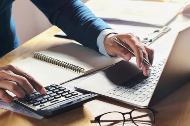 Homem fazendo cálculos no computador e com caderno aberto.