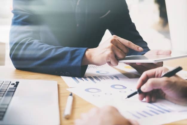 Homens acompanham notícias do mercado financeiro e analisam indicadores